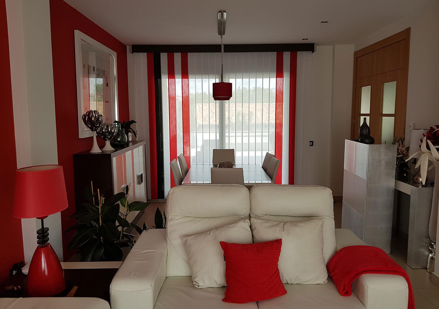 Salón decorado con cortinas verticales combinadas y galería decorativa.